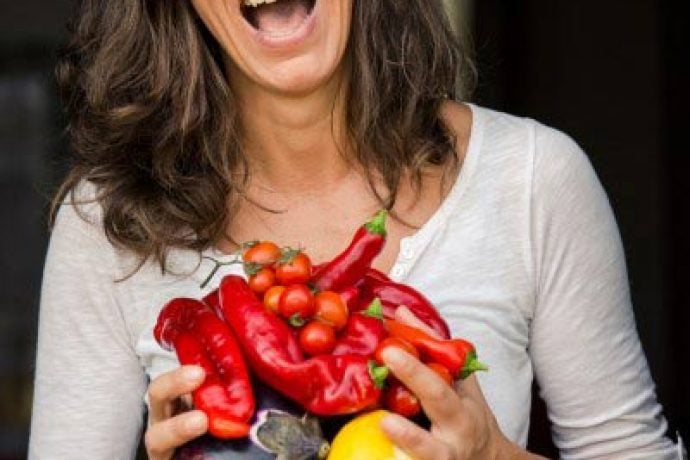 italian female chef with fresh vegetables laughing