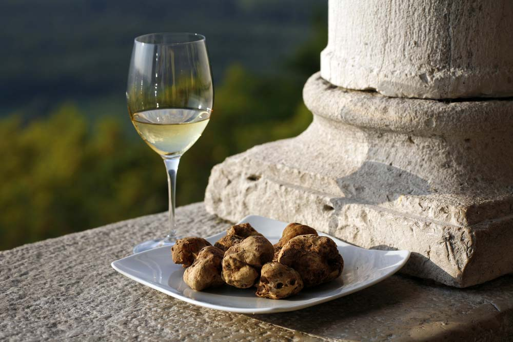 A glass of wine with a plate full of Tuscan black truffles