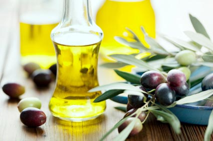 Extra virgin olive oil surrounded by Tuscan olives