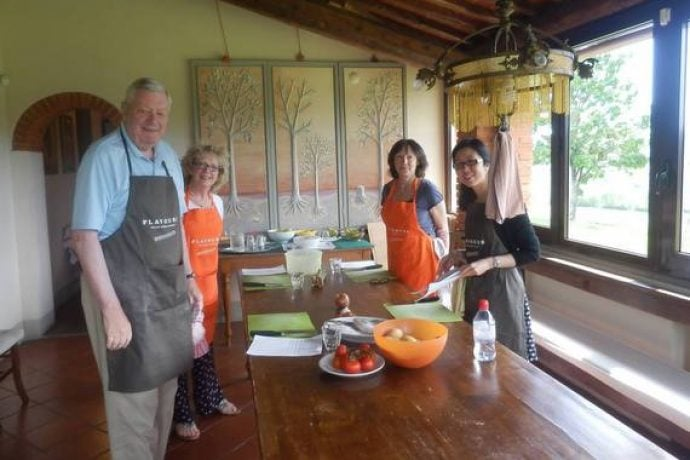 Cooking guests with aprons in Tuscany kitchen during cookery lesson.
