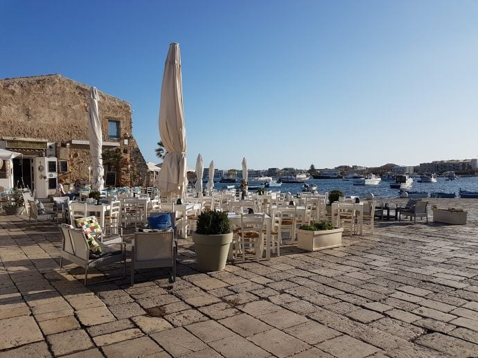 Tables and chairs with a view of Marzamemi harbour