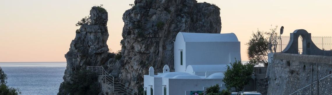 Breathtaking view of Amalfi coast and white house set on top of cliff