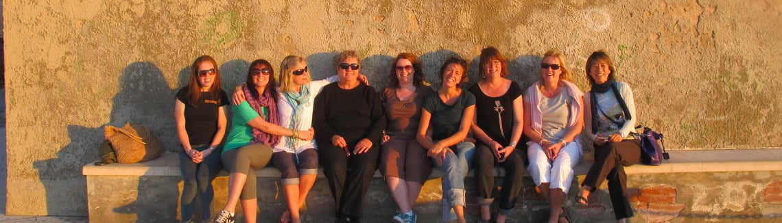 Group of ladies enjoying evening sunshine on bench in front of stone wall