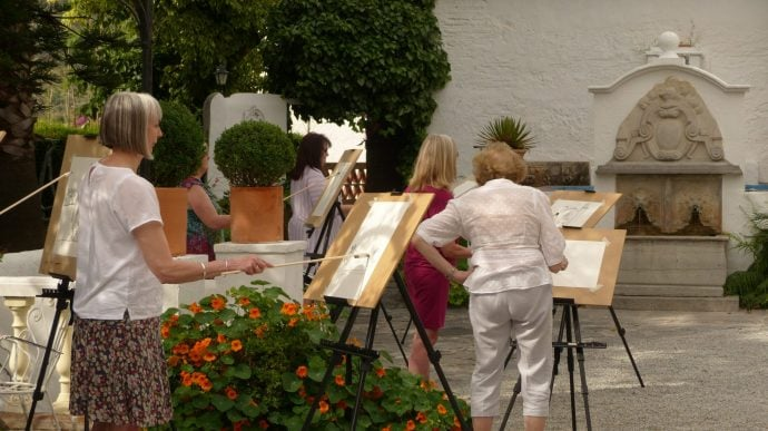 Group of mature women painting in a courtyard