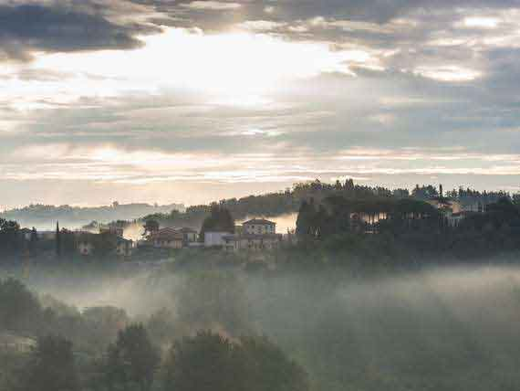 Stunning view of rural Tuscany, rolling hill tops and trees at dusk.