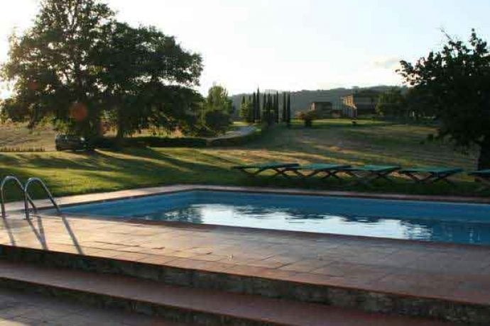 Sunny outdoor area and pool of villa Arezzo in Tuscany.