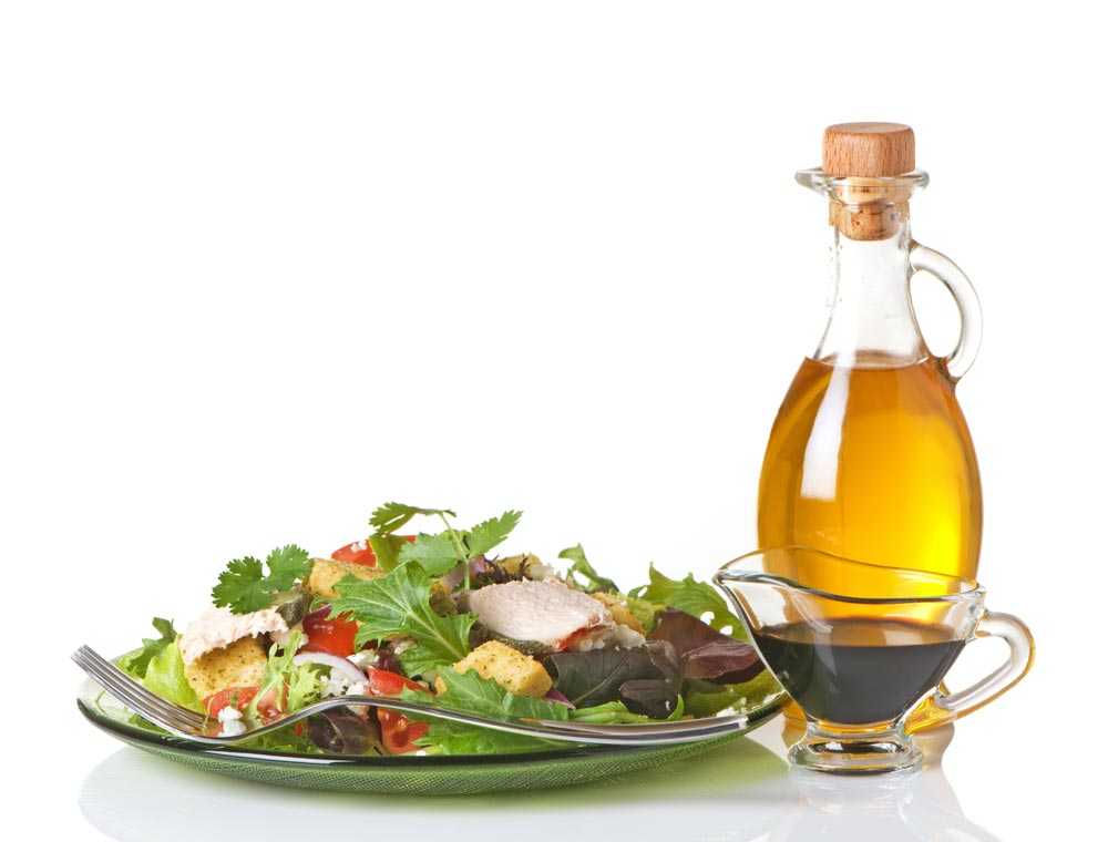 Deliciously fresh salad with a bottle of authentic Italian olive oil.