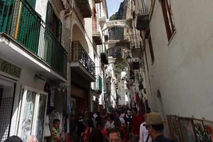 Narrow Italian streets filled with people walking up and down.