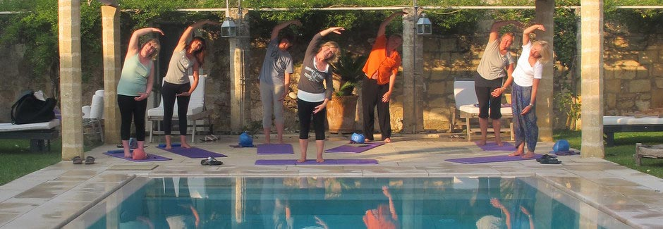 guests doing pilates by pool in sun