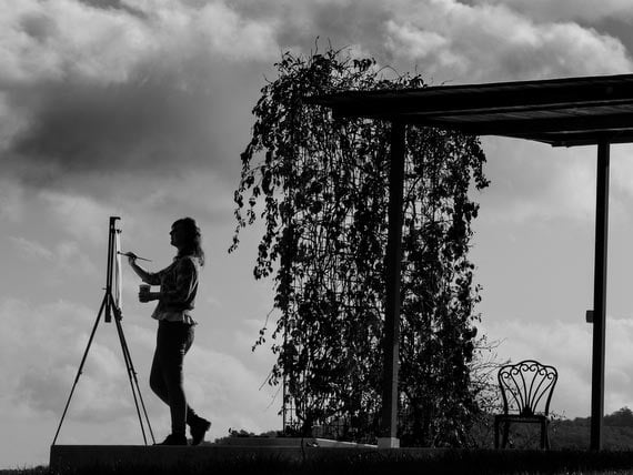 Black and white picture of guest painting Tuscan landscape