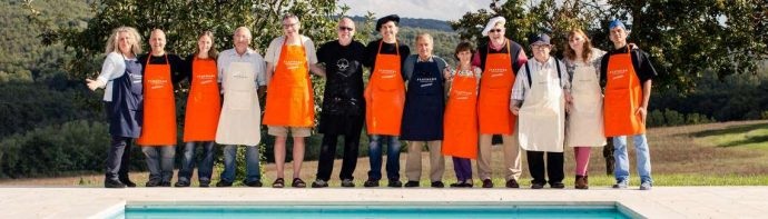 Group of cooking guests wearing aprons and standing arm in arm besides pool