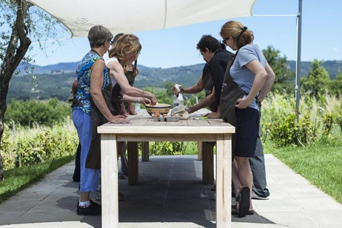 Cookery group with Italian chef showing pasta dough in the Tuscan countryside.