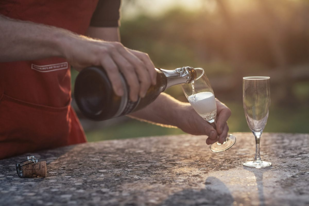Flavours host pouring prosecco into glass