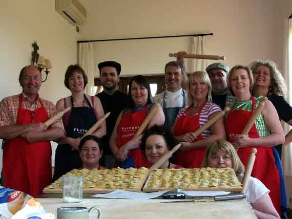 Cookery group with Italian chef showing their freshly made pasta.