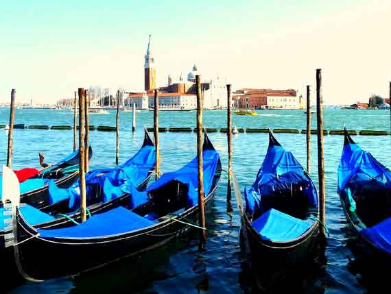 Venice's infamous gondolas floating in the water with the city of Venice in the background