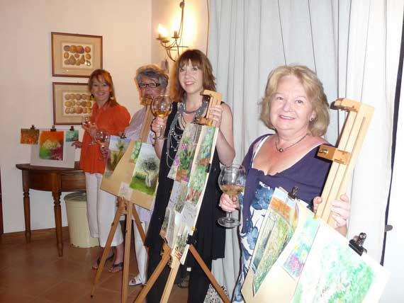 4 artists beside easel displaying their paintings