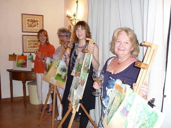 4 artists beside easel displaying their paintings