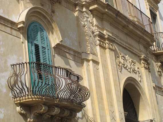 Impressive old stone building with a balcony in Sicily