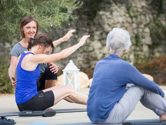 Instructor helping guests with Pilates pose