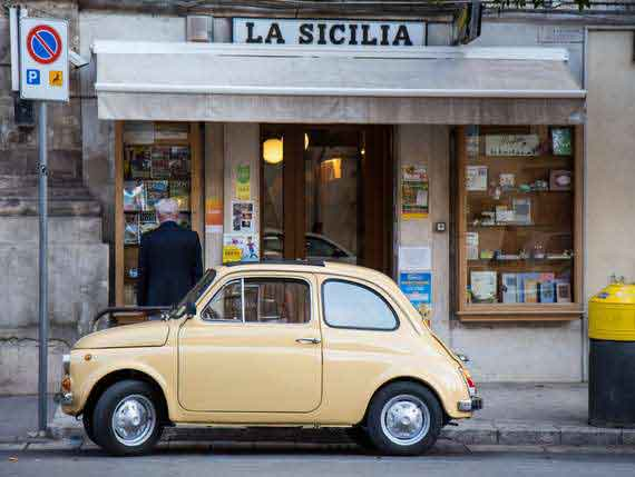 Small Italian car in front of house with Sicily sign.