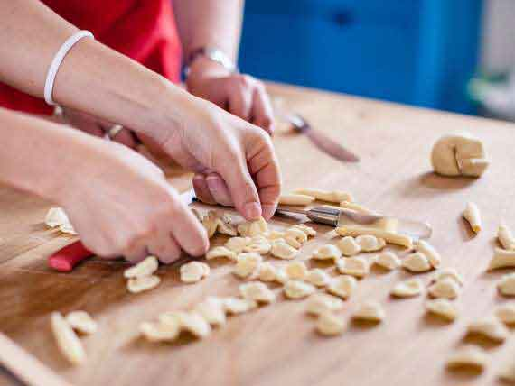 Cooking guests preparing home made pasta on cooking holiday in Amalfi.