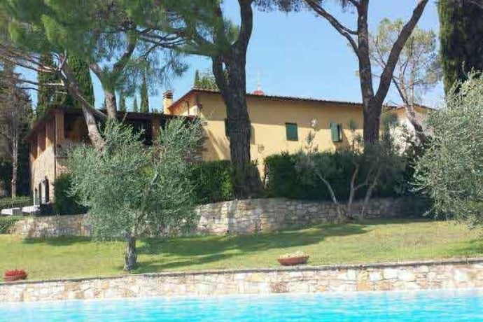 Old, stone holiday villa with mature trees in Tuscany