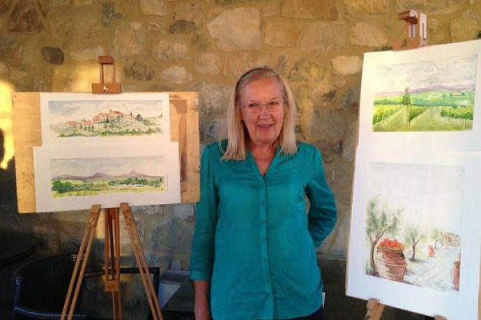 Female guest standing next to two easels showing watercolour paintings of Tuscan landscape.