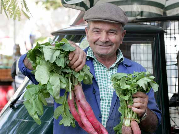 Elderly Italian man holding vegetables at a food market in Tuscany