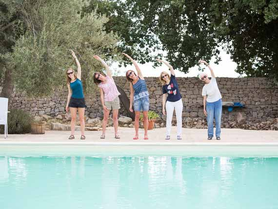 Five women standing at pool and doing Pilates pose