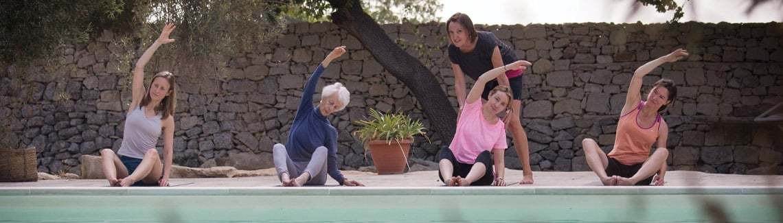 Pilates group with instructor doing Pilates outside at the pool