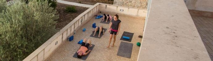 Pilates and teacher with Pilates guest on outside terrace in Sicily