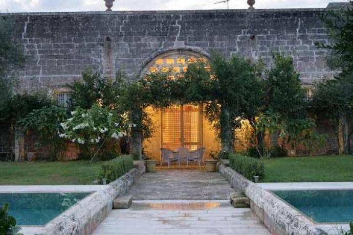 Puglia villa from outside in idyllic garden.
