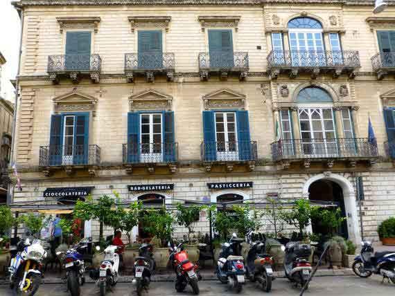 Vespas in front of Sicilian building.