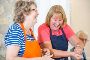 ladies cooking and laughing during italian cookery course