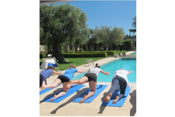 Pilates students exercising outside at the pool in the Italian sun