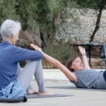 Pilates instructor demonstrating Pilates pose to guests at pool