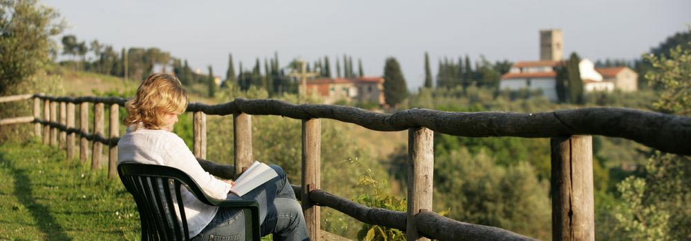 Woman sitting on chair whilst painting Tuscan countryside