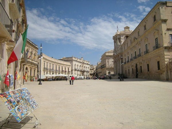 Panorama shot of Piazza del Duomo (Cathedral Square) in Syracuse (Siracusa), Sicily with Italian flag, postcards and restaurants