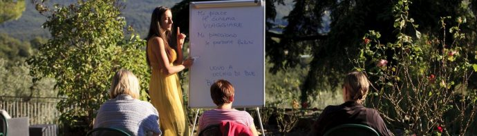 Italian language teacher with students writing on white board in Tuscany