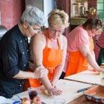 Italian chef Francesca teaching guest how to knead pasta dough