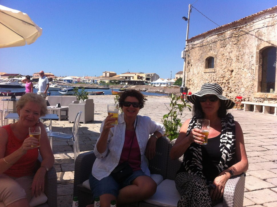painting guests in sicily with drinks in sun