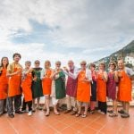Group of cooking guests with aprons enjoying Amalfi outside