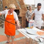 Woman making pizza outside in Italy
