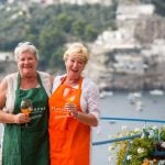 Women on cooking holiday laughing and enjoying glass of Prosecco