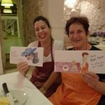 Two Italian women with aprons holding sketches from holiday