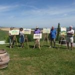 Group of students standing in Italian landscape next to easels and watercolour paintings