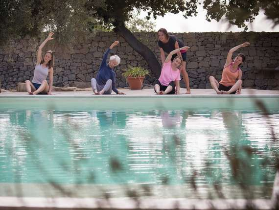Pilates students exercising by the pool in Sicily