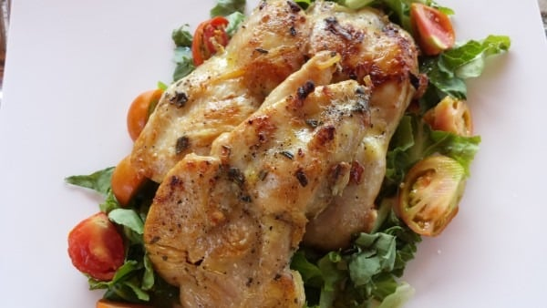 A plate of marinated chicken pieces on a bed of salad leaves