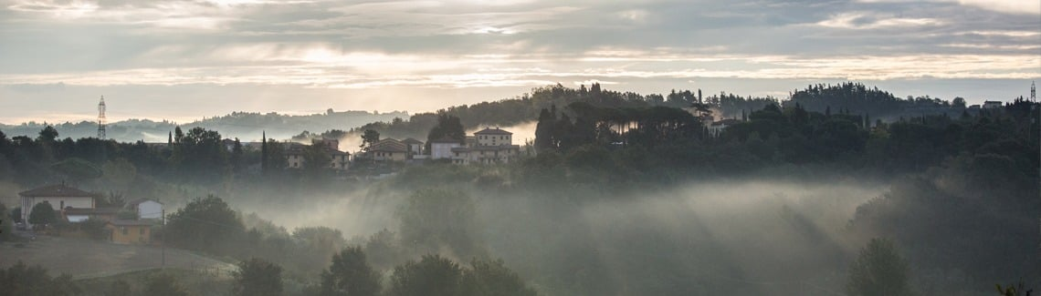 Tuscan village in morning fog