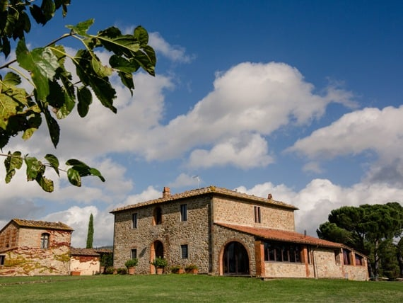 View of rustic Tuscan villa surrounded by cypress trees.